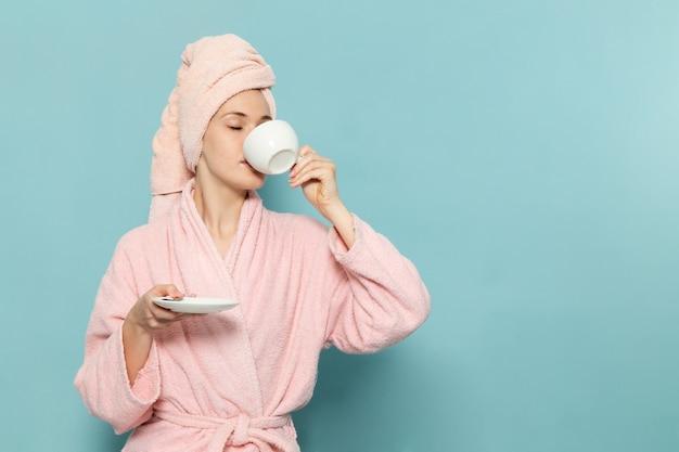 Junge frau im rosa bademantel nach der dusche, die kaffee auf blau trinkt