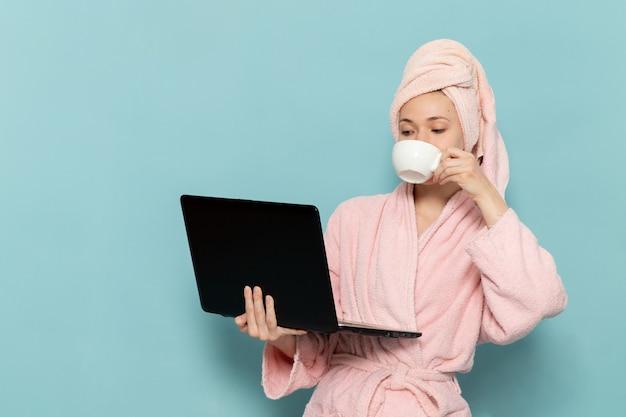 Junge frau im rosa bademantel nach der dusche, die kaffee trinkt und laptop auf blau verwendet