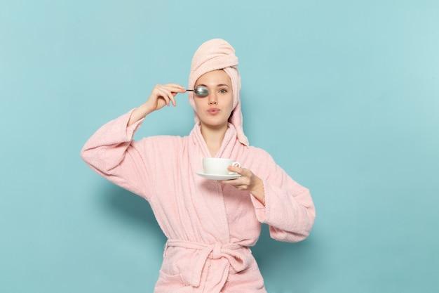 Junge frau im rosa bademantel nach der dusche, die kaffeetasse auf blau hält