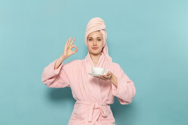 Junge frau im rosa bademantel nach der dusche, die tasse kaffee auf blau hält