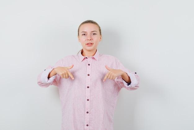 Junge frau im rosa hemd, das nach unten zeigt und positiv schaut