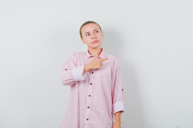 Junge frau im rosa hemd, das zur seite zeigt und unzufrieden aussieht