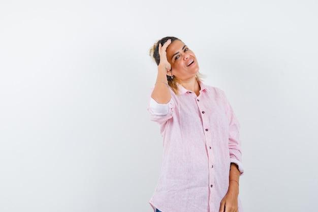 Junge frau im rosa hemd, die hand auf kopf hält und fröhlich schaut