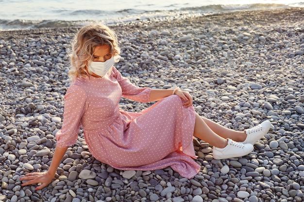 Junge frau im rosa kleid und in der schützenden gesichtsmaske sitzt nachdenklich allein auf kieselstrand