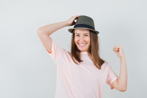 Junge frau im rosa t-shirt, hut, der mit hand auf kopf aufwirft und attraktive vorderansicht schaut.