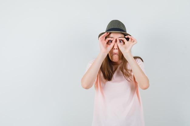 Junge frau im rosa t-shirt, hut zeigt brillengeste und schaut lustig, vorderansicht.