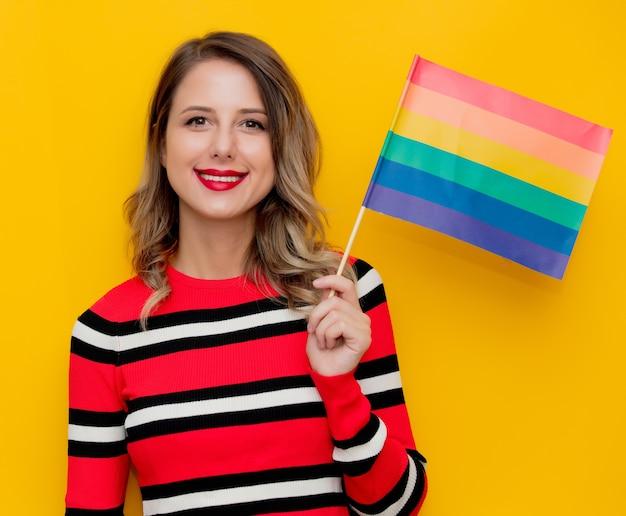 Junge frau im rot gestreiften pullover mit lgbt-flagge auf gelb