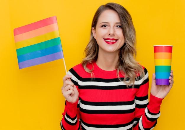 Junge frau im rot gestreiften pullover mit tasse und lgbt-flagge auf gelb