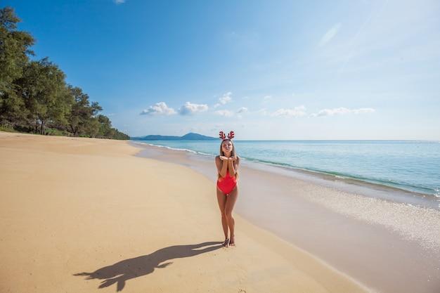 Junge frau im roten badeanzug, der die lustigen weihnachtsrengeweihe senden luftkuß auf dem strand trägt