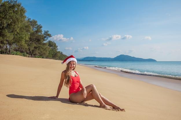 Junge frau im roten badeanzug und in weihnachtsmann-hut, die auf dem breiten leeren tropischen strand sitzen