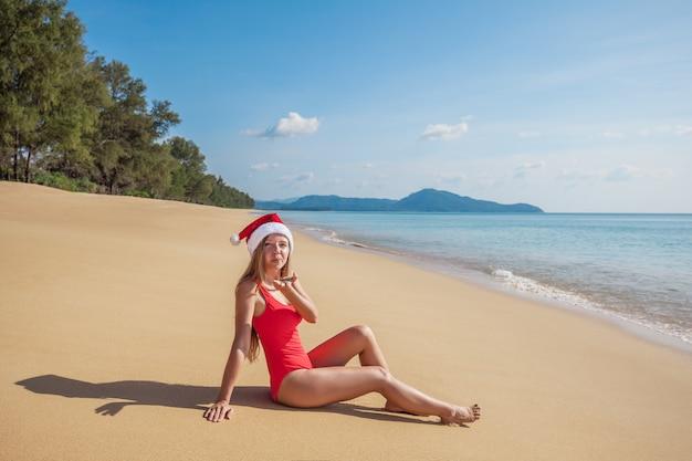 Junge frau im roten badeanzug und in weihnachtsmann-hut, die den luftkuß sitzt auf dem leeren strand sendet