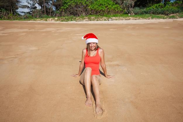 Junge frau im roten badeanzug und in weihnachtsmann-hut, die kamera betrachten