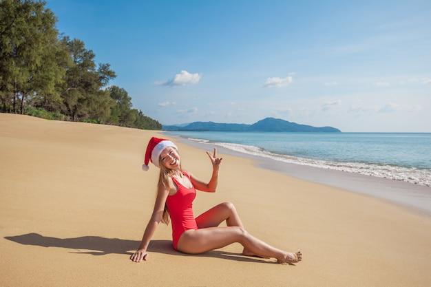 Junge frau im roten badeanzug und in weihnachtsmann-hut zeigen v-zeichengeste auf dem strand