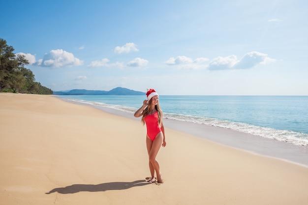 Junge frau im roten badeanzug und weihnachtsmann mütze am strand