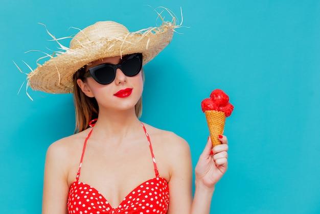 Junge frau im roten bikini und im strohhut mit eiscreme