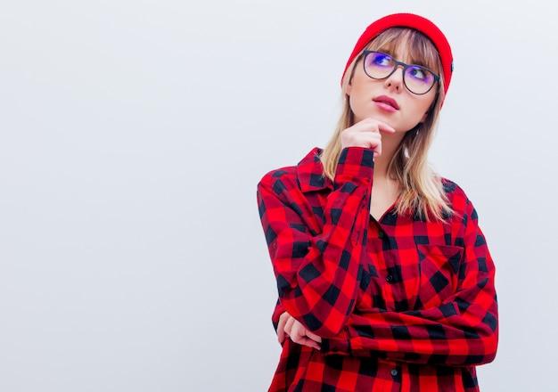 Junge frau im roten hemd und im hut mit gläsern