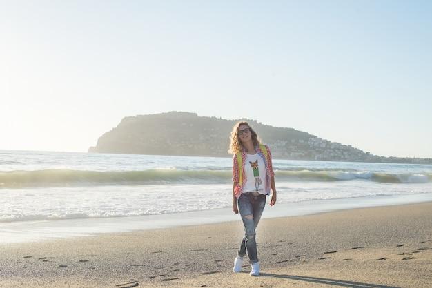 Junge frau im roten karierten hemd, in den jeans, in den weißen turnschuhen gehend entlang strand und im stürmischen ozean am sonnigen wintertag