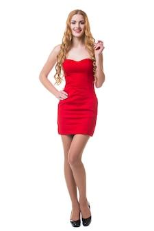 Junge frau im roten kleid, das auf weißem hintergrund tanzt