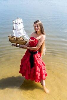 Junge frau im roten kleid, das schiffsmodell an der küste hält