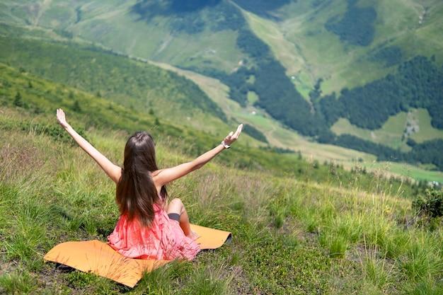 Junge frau im roten kleid, die an einem windigen tag in den sommerbergen auf einer grasbewachsenen wiese sitzt, hebt ihre hände und genießt den blick auf die natur.