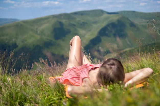 Junge frau im roten kleid liegt auf einer grünen wiese und ruht an einem sonnigen tag in den sommerbergen mit blick auf die natur.