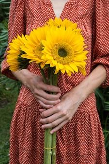 Junge frau im roten kleid mit einem großen strauß sonnenblumen