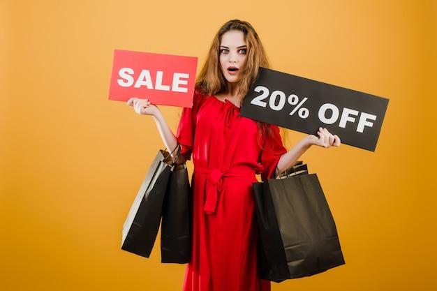 Junge frau im roten kleid mit verkauf 20% zeichen und papiereinkaufstaschen lokalisiert über gelb
