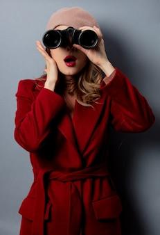 Junge frau im roten mantel mit binokeln