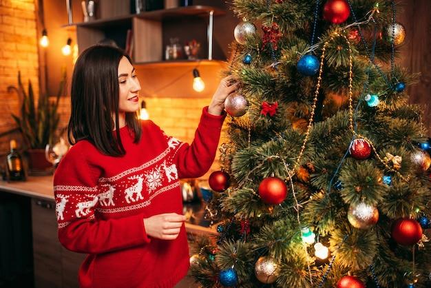 Junge frau im roten pullover schmücken weihnachtsbaum. weihnachtsfeier, hausfeiertag