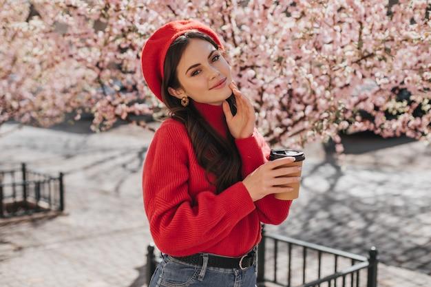 Junge frau im roten pullover und im hut hält pappbecher kaffee. junge dame, die mit teeglas aufwirft und aufrichtig gegen blühende sakura lächelt