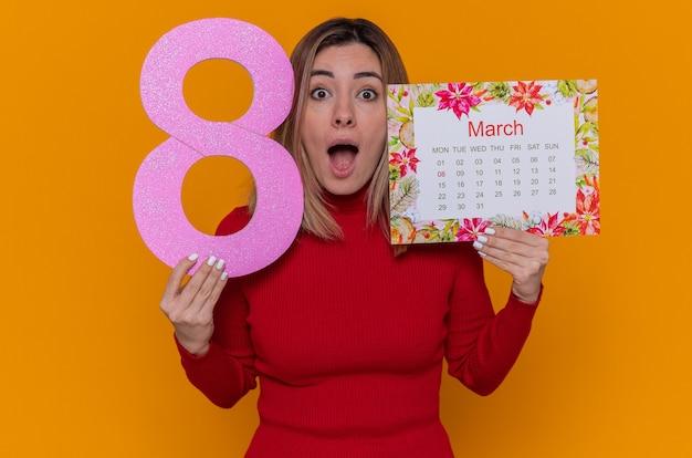 Junge frau im roten rollkragenpullover, der papierkalender des monats märz und nummer acht hält
