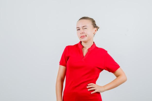 Junge frau im roten t-shirt, das auge zwinkert und hand auf taille hält
