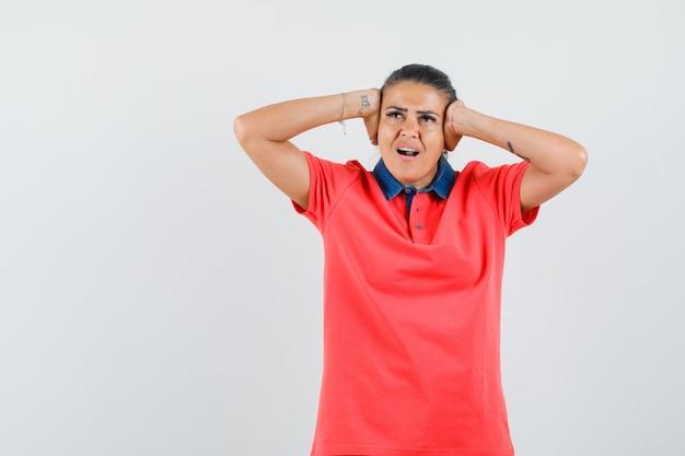 Junge frau im roten t-shirt, das hände auf ohr drückt und gehetzt, vorderansicht schaut.