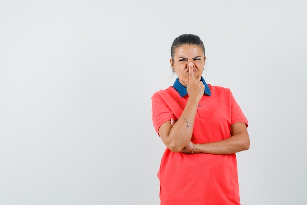 Junge frau im roten t-shirt, das in der denkenden haltung steht und zeigefinger auf nase setzt und gehetzt, vorderansicht schaut.