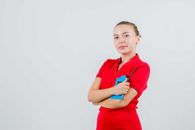 Junge frau im roten t-shirt, das mini-klemmbrett hält und optimistisch schaut