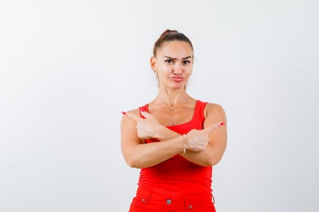 Junge frau im roten trägershirt, hose zeigt auf beide seiten und sieht zögernd aus, vorderansicht.