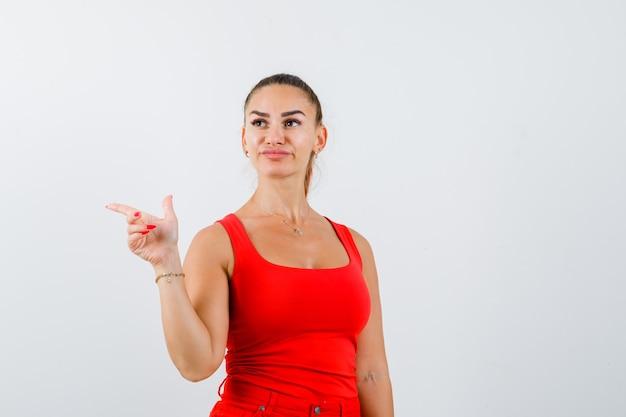 Junge frau im roten trägershirt, hose zeigt auf die linke seite und sieht zögernd aus, vorderansicht.