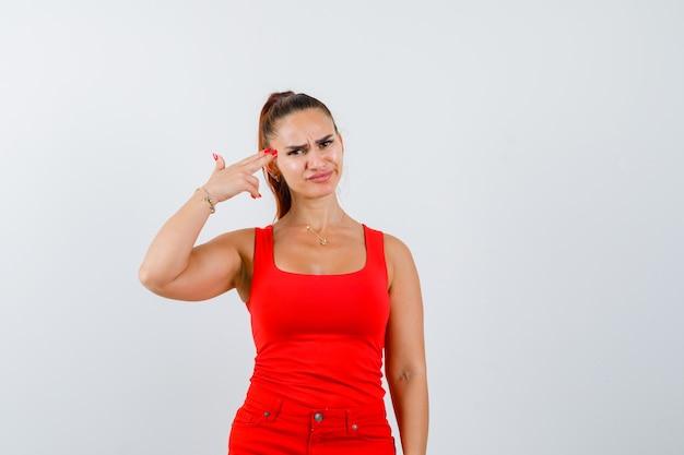 Junge frau im roten trägershirt, hosen, die pistolenhandzeichen zeigen und enttäuscht schauen, vorderansicht.