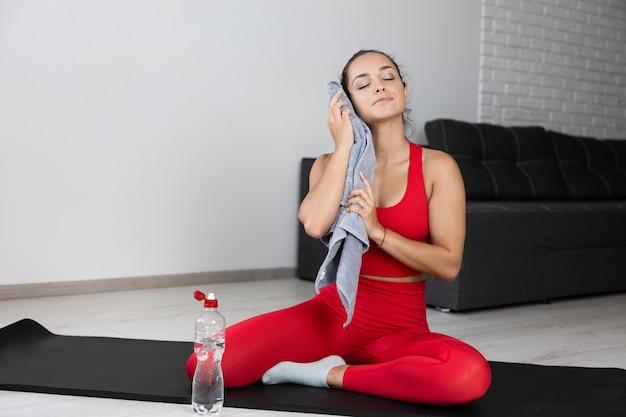 Junge frau im roten trainingsanzug, der übung oder yoga zu hause tut. wohlbefinden mädchen mit handtuch für schweiß nach hartem training oder training in der wohnung. geöffnete wasserflasche. genieße ihre ruhe zu hause.