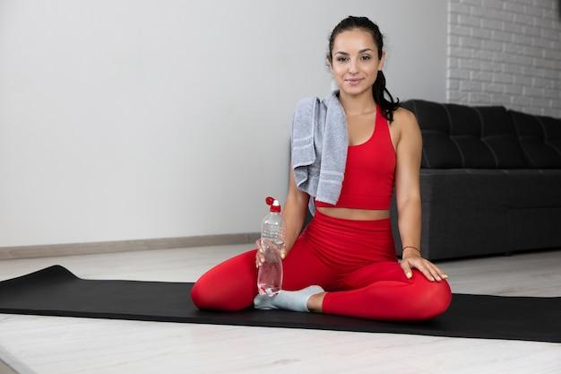 Junge frau im roten trainingsanzug, der übung oder yoga zu hause tut. zuversichtlich positiv sportlich gut gebaut modellhold wasserflasche in der hand und handtuch auf der schulter. werbung. sport-life-balance.