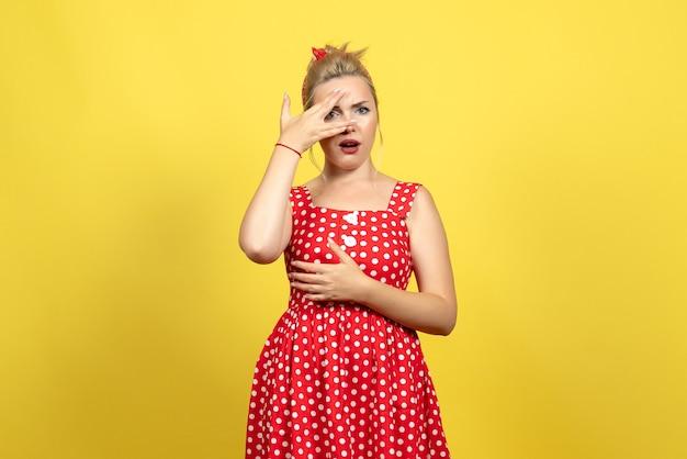 Junge frau im roten tupfenkleid, das auf gelb aufwirft