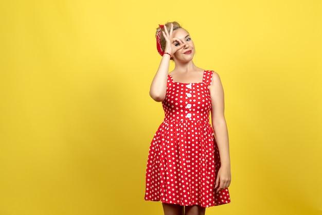 Junge frau im roten tupfenkleid, das auf gelbem bodenkleid frau mode alte farbe retro aufwirft