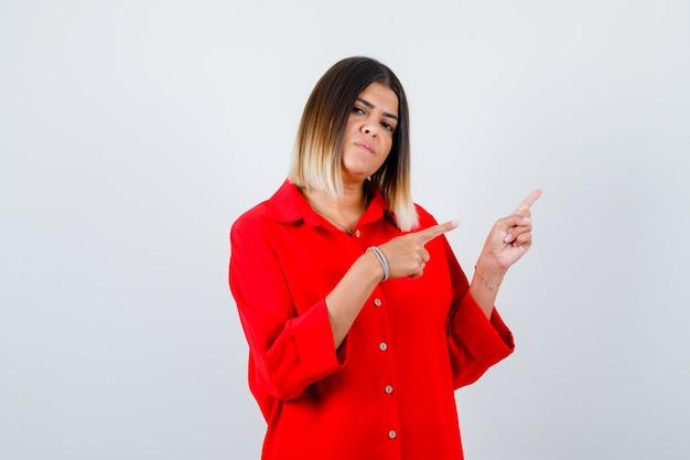 Junge frau im roten übergroßen hemd, das auf die obere rechte ecke zeigt und selbstbewusst aussieht, vorderansicht.