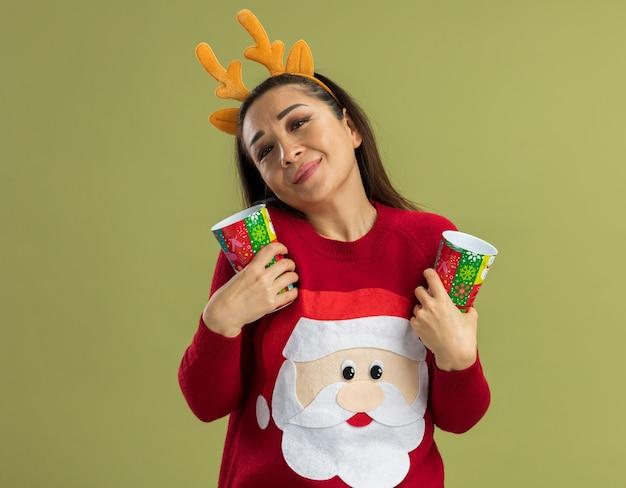 Junge frau im roten weihnachtspullover, der lustigen rand mit hirschhörnern hält, die bunte pappbecher halten, die positive gefühle lächelnd fühlen