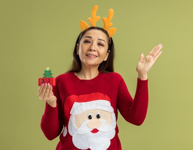 Junge frau im roten weihnachtspullover, der lustigen rand mit hirschhörnern hält, die spielzeugwürfel mit neujahrsdatum betrachten, das kamera glücklich und fröhlich lächelnd mit dem arm angehoben steht, der über grünem hintergrund steht