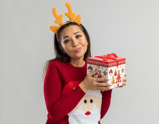 Junge frau im roten weihnachtspullover, der lustigen rand mit hirschhörnern hält, die weihnachtsgeschenk halten, das mit skeptischem lächeln schaut