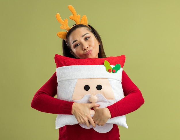 Junge frau im roten weihnachtspullover, der lustigen rand mit hirschhörnern hält, die weihnachtskissen betrachten kamera mit traurigem ausdruck stehen über grünem hintergrund