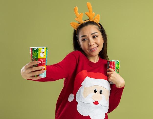 Junge frau im roten weihnachtspullover, der lustigen rand mit hirschhörnern trägt, die bunte pappbecher glücklich und positiv lächelnd fröhlich halten