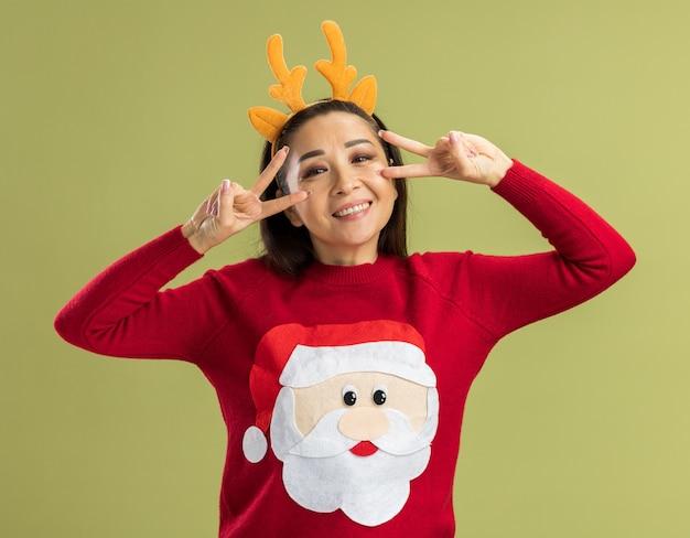 Junge frau im roten weihnachtspullover, der lustigen rand mit hirschhörnern trägt, die kamera betrachten, die mit glücklichem gesicht lächelt, das v-zeichen nahe ihren augen über grünem hintergrund stehend zeigt