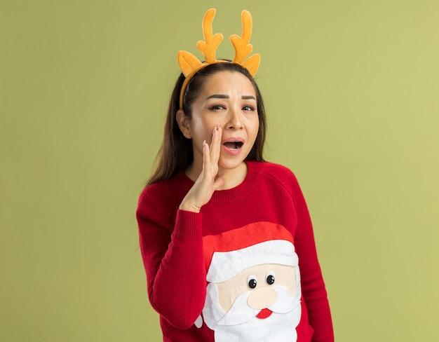 Junge frau im roten weihnachtspullover, der lustigen rand mit hirschhörnern trägt, die mit hand nahe mund schreien